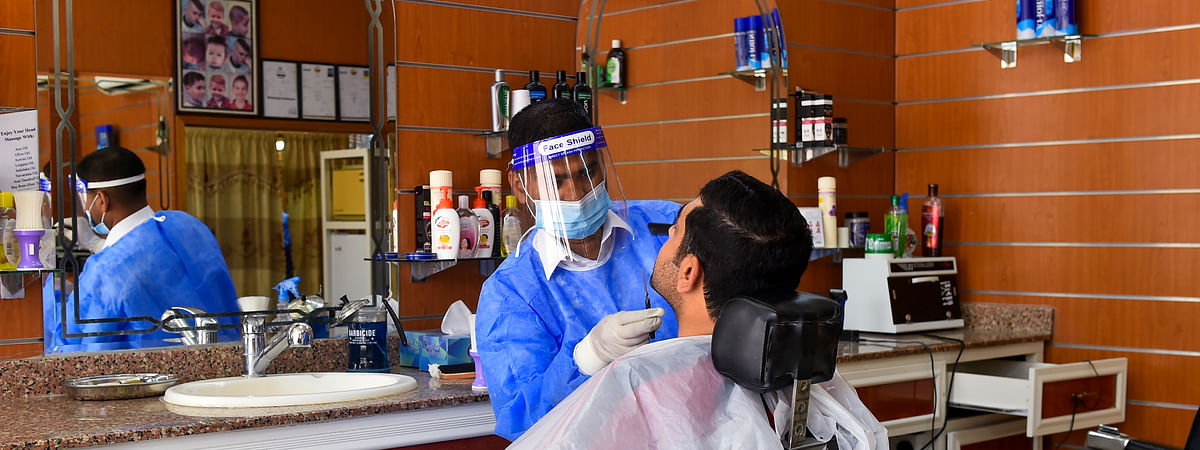 A barber wearing personal protective equipment serves a customer in Doha, capital of Qatar, on July 30, 2020.