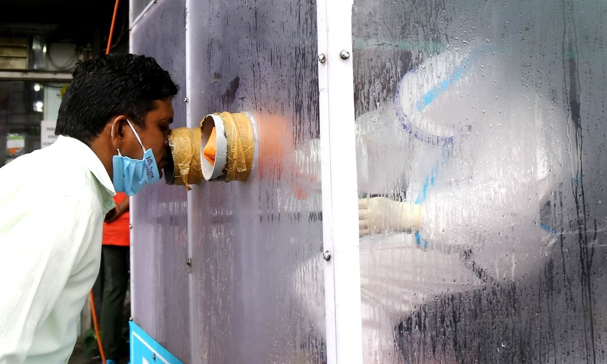 Health workers collecting swab samples for at a mobile COVID-19 testing centre, in New Delhi, on August 13, 2020.