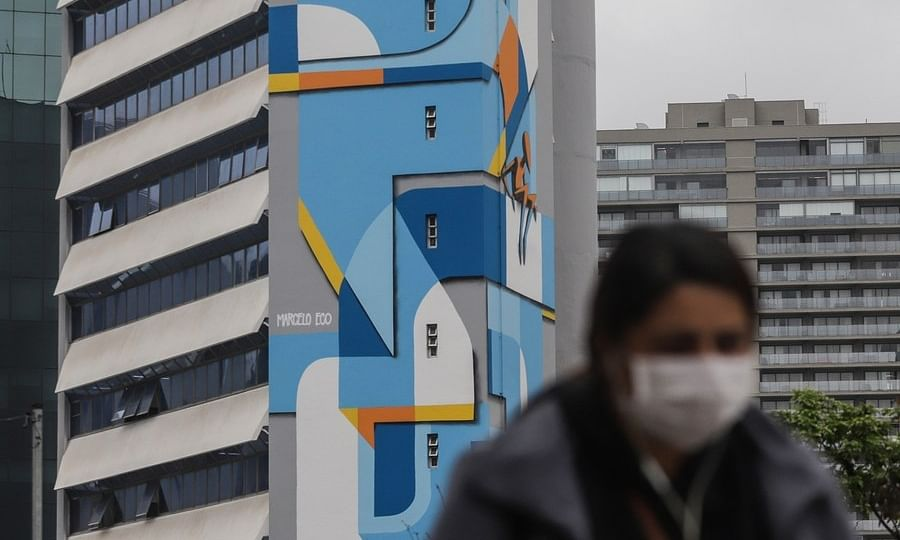 """A woman passes by a graffiti work of """"NaLata International Festival of Urban Art"""" amid the COVID-19 outbreak in Sao Paulo, Brazil, on August 20, 2020. Brazil recorded the lowest one-day COVID-19 death toll in 12 weeks on Sunday."""