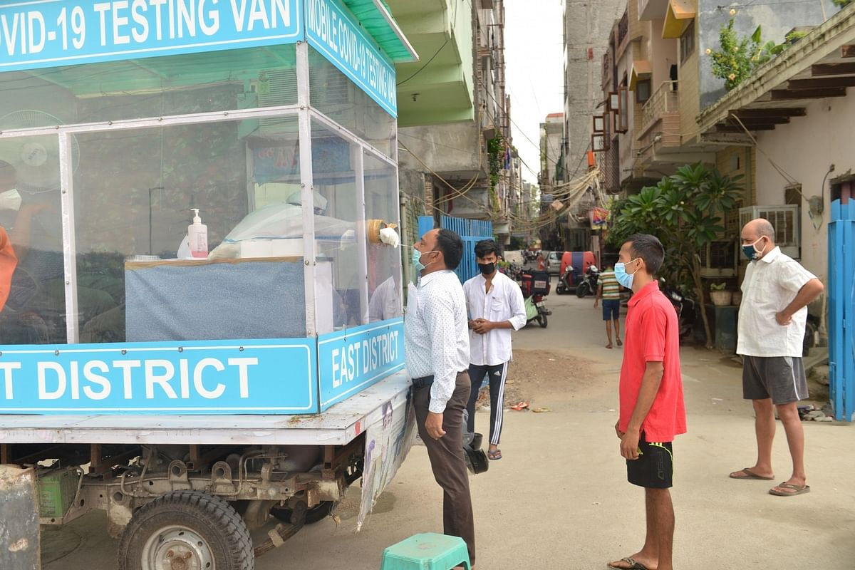 A health worker collecting swab samples from people for COVID-19 testing from a mobile testing van in East Delhi on August 25, 2020