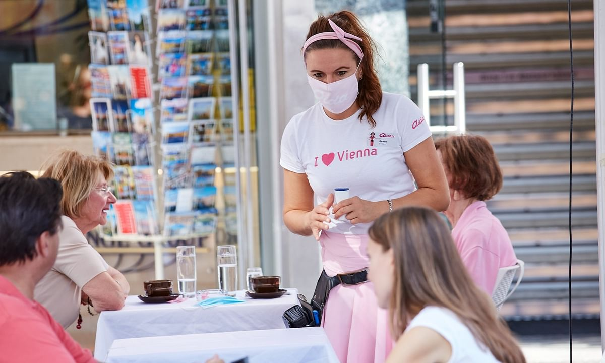 A waitress wearing a face mask serves a table at a restaurant in Vienna, Austria, on September 5, 2020.
