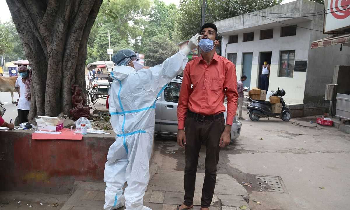 A health worker collecting swab samples from people for COVID-19 rapid antigen tests, in New Delhi on September 24, 2020.