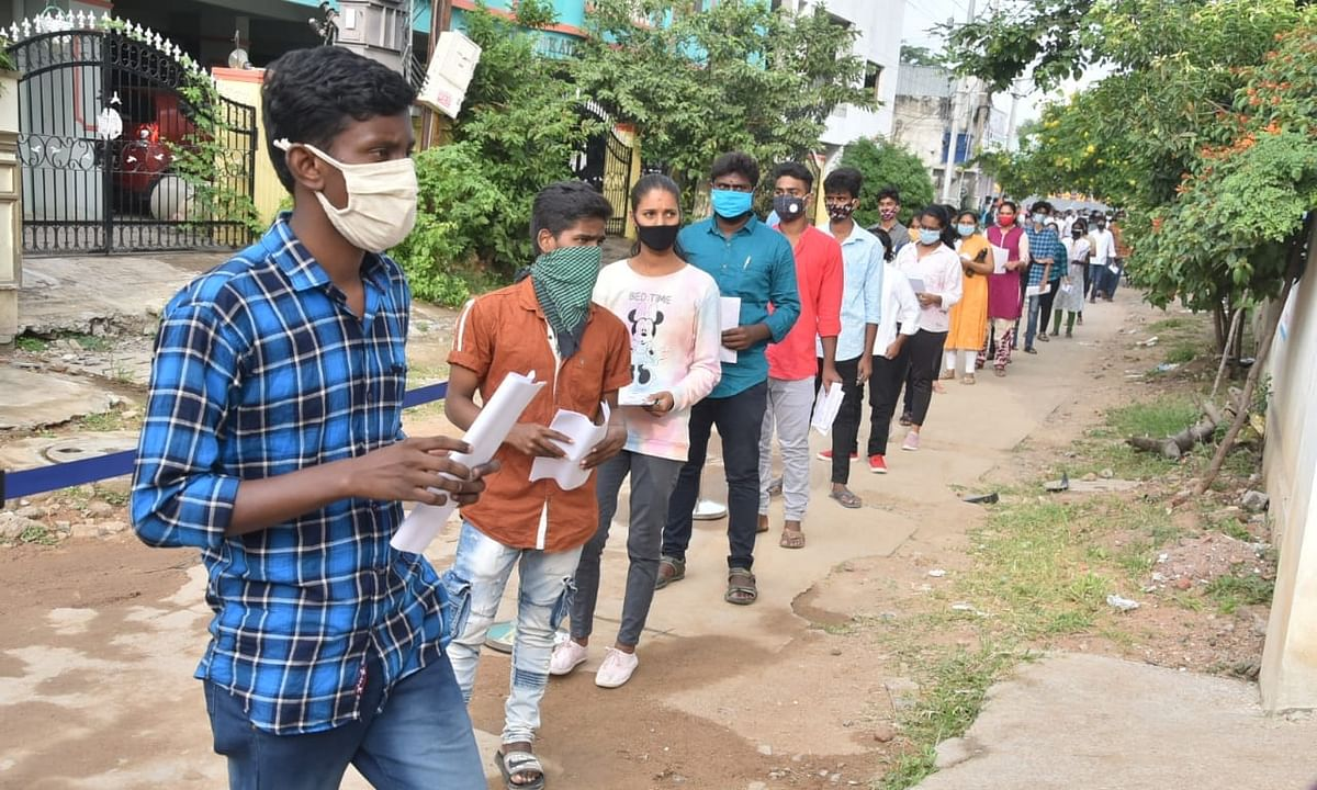 Students appearing for the Telangana State Engineering, Agriculture & Medical (Pharmacy, Veterinary) Common Entrance Test following social distancing as they queue up outside their examination centre in Hyderabad on September 9, 2020.