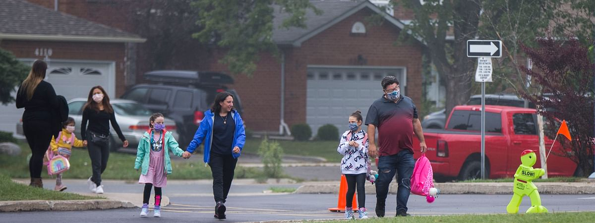Parents and children arrive at a school in Mississauga, Ontario, Canada, on September 9, 2020.  Some schools in Ontario reopened on Wednesday, offering a mix of in-person classes and online learning for students.
