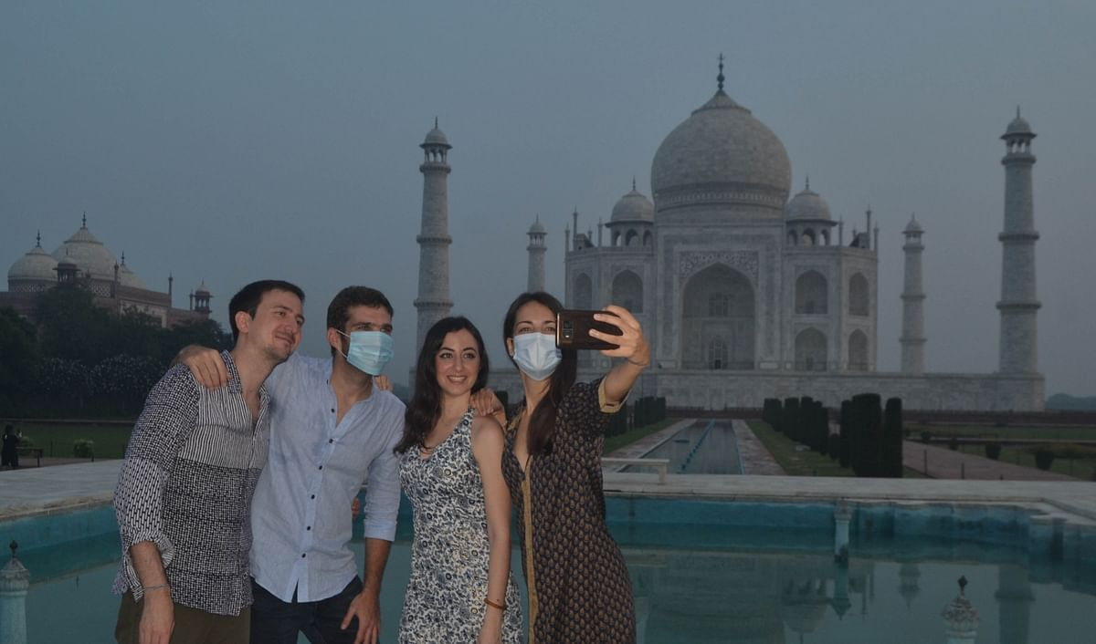 Visitors posing for selfies in front of the Taj Mahal after it reopened in Agra on September 21, 2020 after remaining closed for 188 days due to the COVID-19 pandemic.