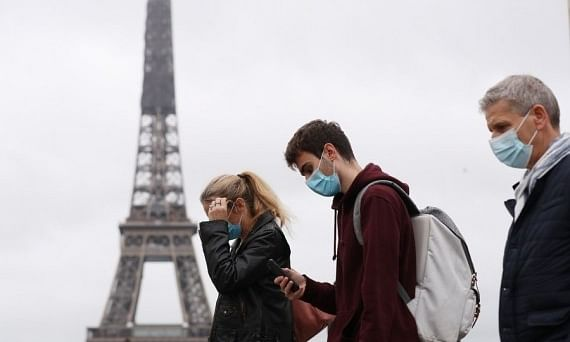 People wearing face masks walking past the Trocadero Place near the Eiffel Tower in Paris, France, on October 23, 2020.
