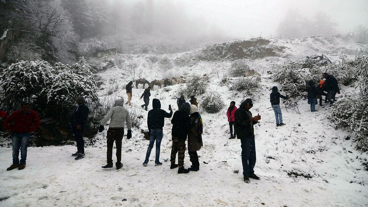 File phot of tourists enjoying themselves during snowfall at Kufri in Shimla, on December 12, 2019.