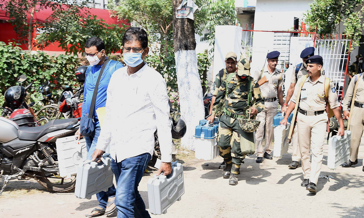 Polling officials and security personnel carrying Electronic Voting Machine (EVMs) and other necessary articles required for the Bihar Assembly Elections, at a distribution centre, at Anugrah Memorial College, Gaya, in Bihar on October 27, 2020.