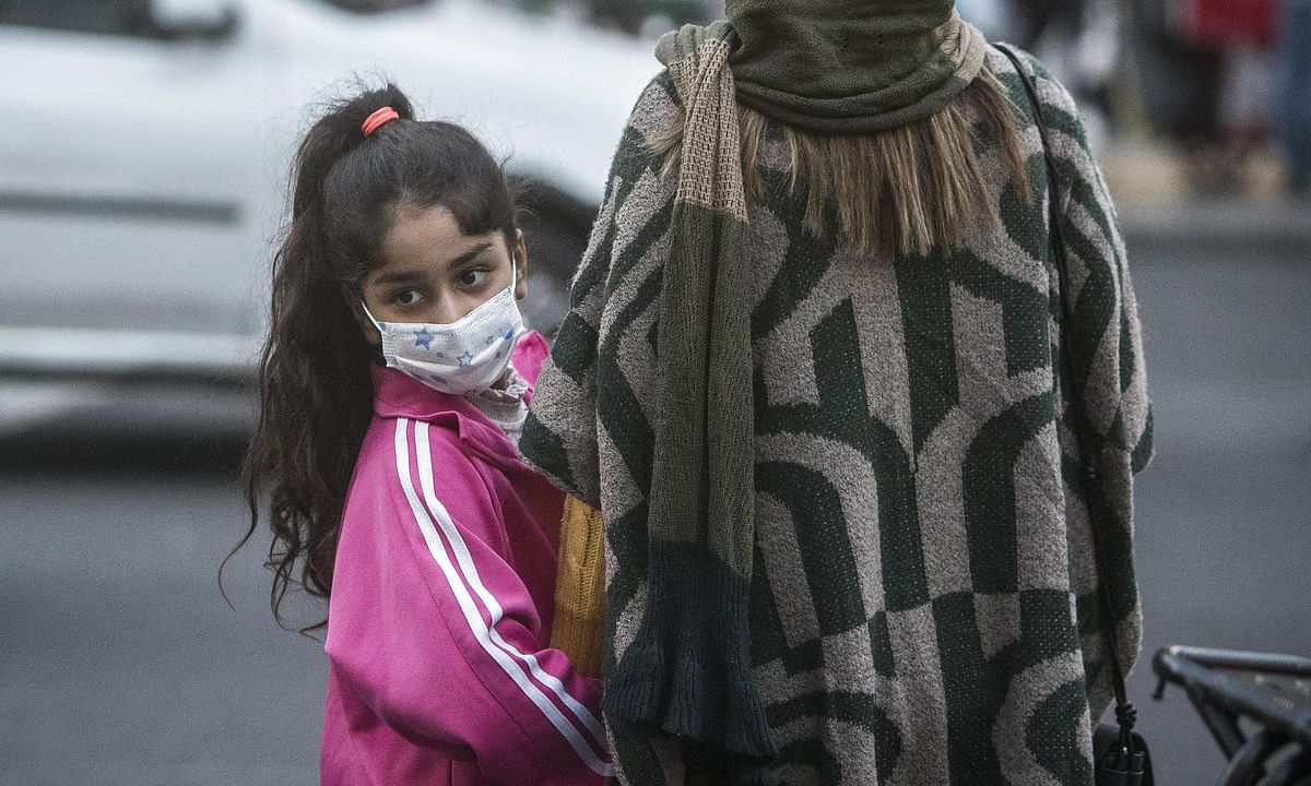A girl wearing a face mask standing beside her mother on a street in Tehran, Iran, on October 12, 2020.