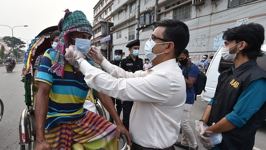 Officials providing a face mask to a rickshaw puller during mobile court drives in Dhaka, Bangladesh on November 19, 2020.