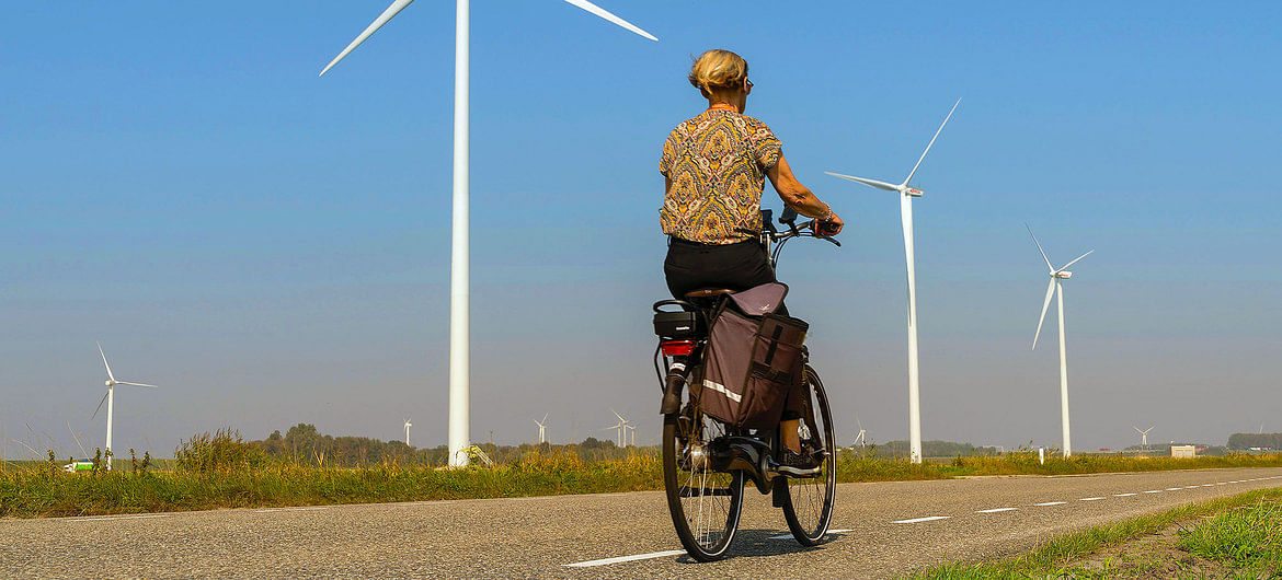 A woman cycling past wind turbines on a country road in Heijningen, The Netherlands.