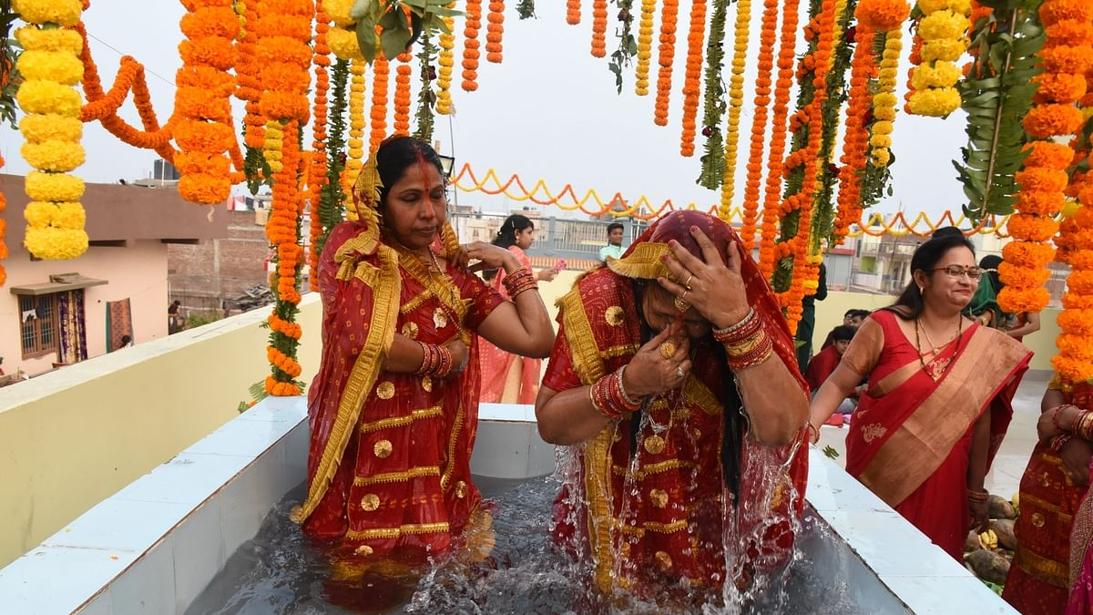 Women performing rituals in an artificial tank created on the terrace of their residence amid the COVID-19 pandemic, during Chhath Puja celebrations in Patna on November 20, 2020.