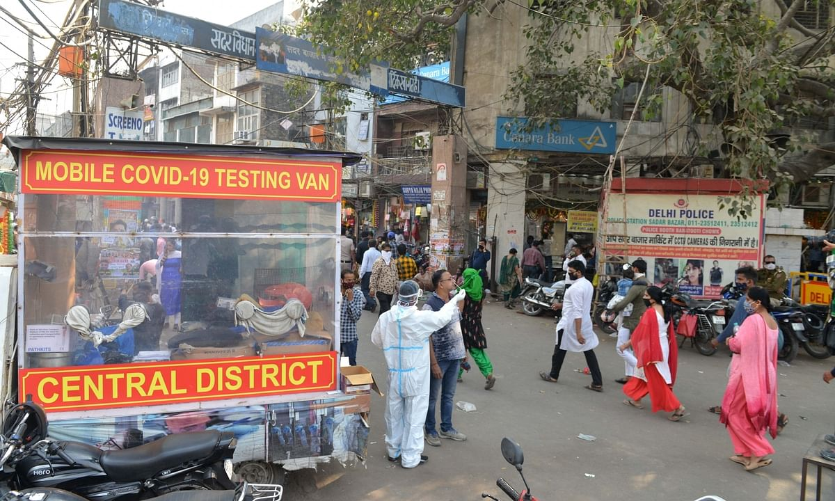 A mobile COVID-19 testing van collecting samples from people for coronavirus testing, at a busy Delhi market on the eve of Diwali on November 13, 2020.