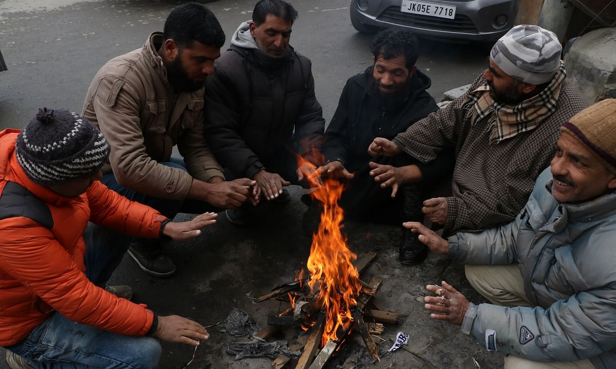 File photo of people warming themselves around a fire on a cold day in Srinagar