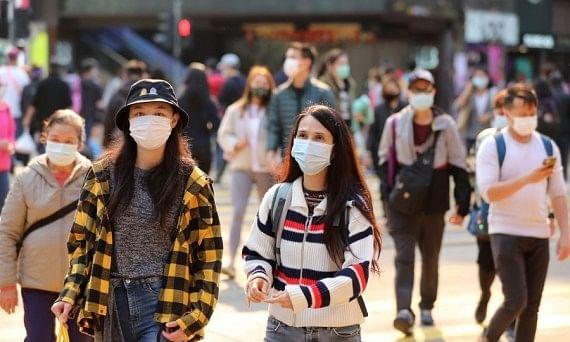 Pedestrians wearing face masks walking on a street in Hong Kong, on December 24, 2020.
