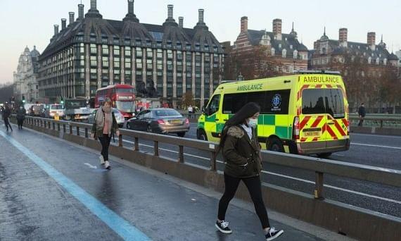 A woman walking across Westminster Bridge, in London, Britain, on November 27, 2020.