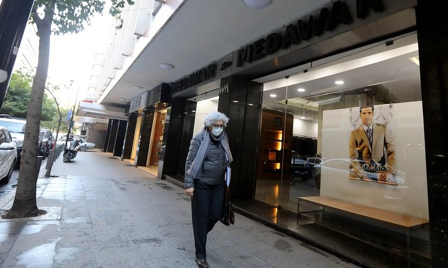 A woman wearing facemask walking past a shop in Hamra, one of the most popular shopping streets in Beirut, capital of Lebanon, on December 29, 2020.