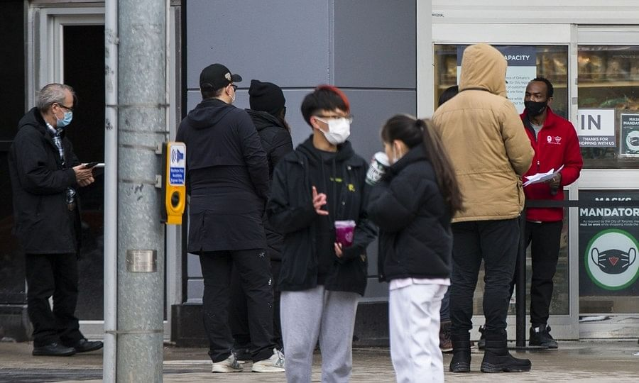 People wearing face masks lining up to pick up their online shopping items outside a store in Toronto, Canada.