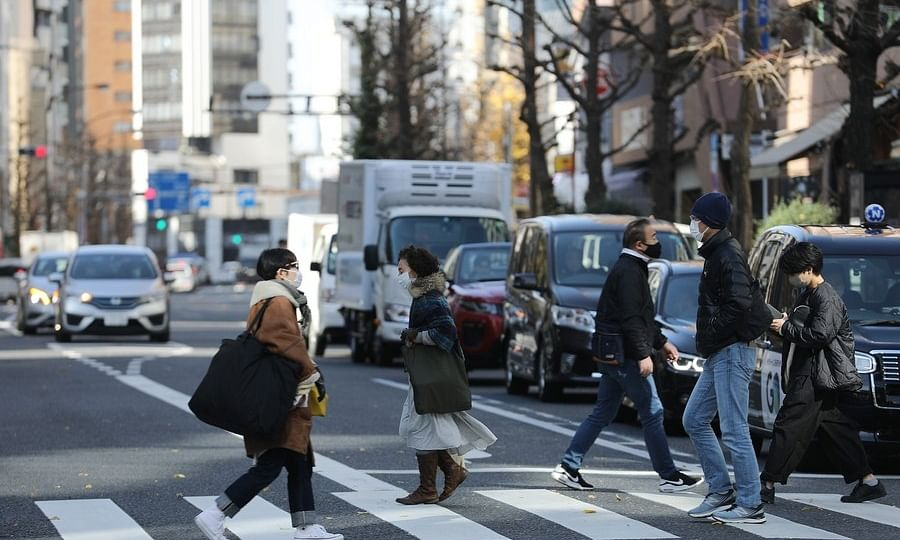 Pedestrians wearing face masks are seen on a road in Tokyo, Japan, on January 7, 2021.