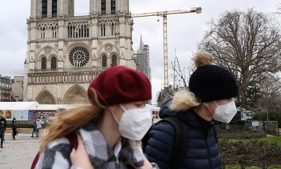 People wearing masks walking past the Notre Dame de Paris cathedral in Paris, France, on February 3, 2021.