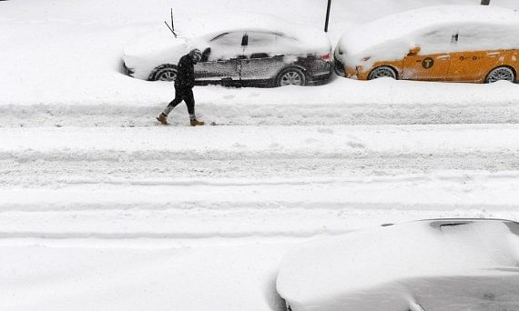 A man walking past snow-covered vehicles in New York, the United States, on February 1, 2021.