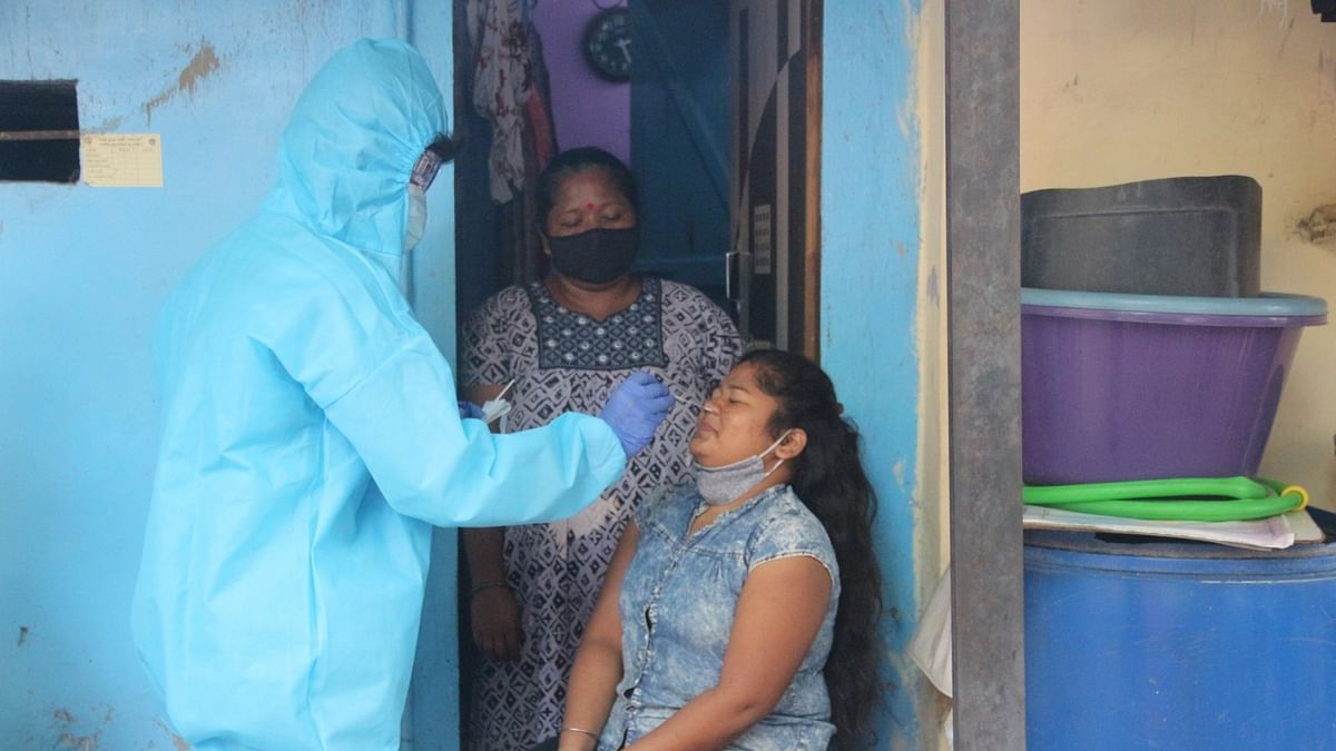 A health worker taking a swab sample of a resident of Dharavi, for COVID-19 test, following a rise in coronavirus cases in the area, in Mumbai on February 23, 2021.