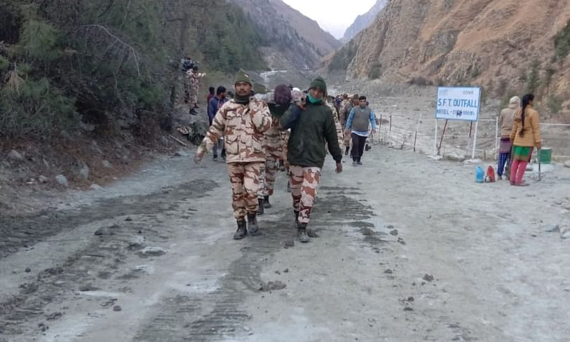 Three persons extricated from a tunnel by ITBP personnel after the glacier burst in Uttarakhand, being carried by ITBP jawans on stretchers to nearest road head, on February 7, 2021.