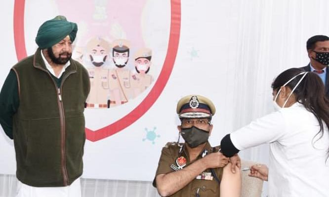Punjab Director General of Police Dinkar Gupta becoming the first from one the police force to get vaccinated against COVID-19 after Chief Minister Amarinder Singh (standing, left) launched the second phase of the COVID-19 vaccination drive for frontline workers, in Chandigarh on February 2, 2021.