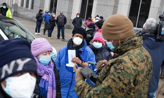 People registering with National Guard members outside the mass vaccination site at Yankee Stadium in the Bronx borough of New York, the United States, on February 5, 2021.