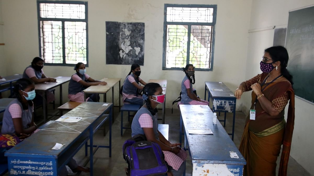A teacher and her students, all wearing masks, in a school in Chennai.