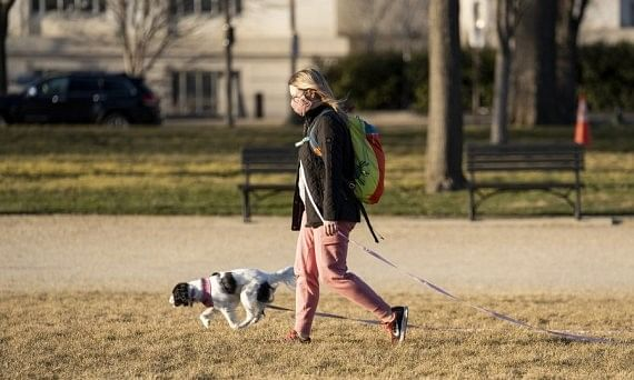 A woman wearing a face mask walking a dog in Washington, D.C., in the United States, on March 3, 2021.
