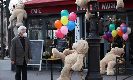 A man wearing a mask looking at giant teddy bears outside a restaurant in Paris, France, on March 3, 2021.