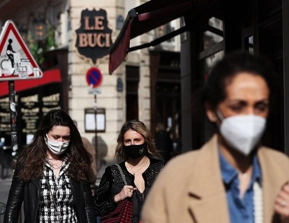 People wearing masks walking on a street in Paris, France on March 3, 2021.