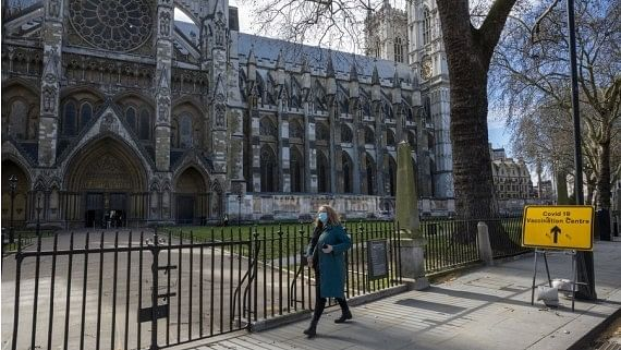 A woman walking past the COVID-19 Vaccination Centre in Westminster Abbey in London, Britain on March 11, 2021.