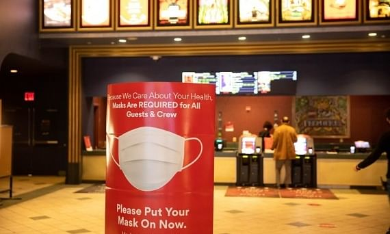 A sign about face mask requirements is seen at a movie theater in New York, the United States, March 5, 2021.