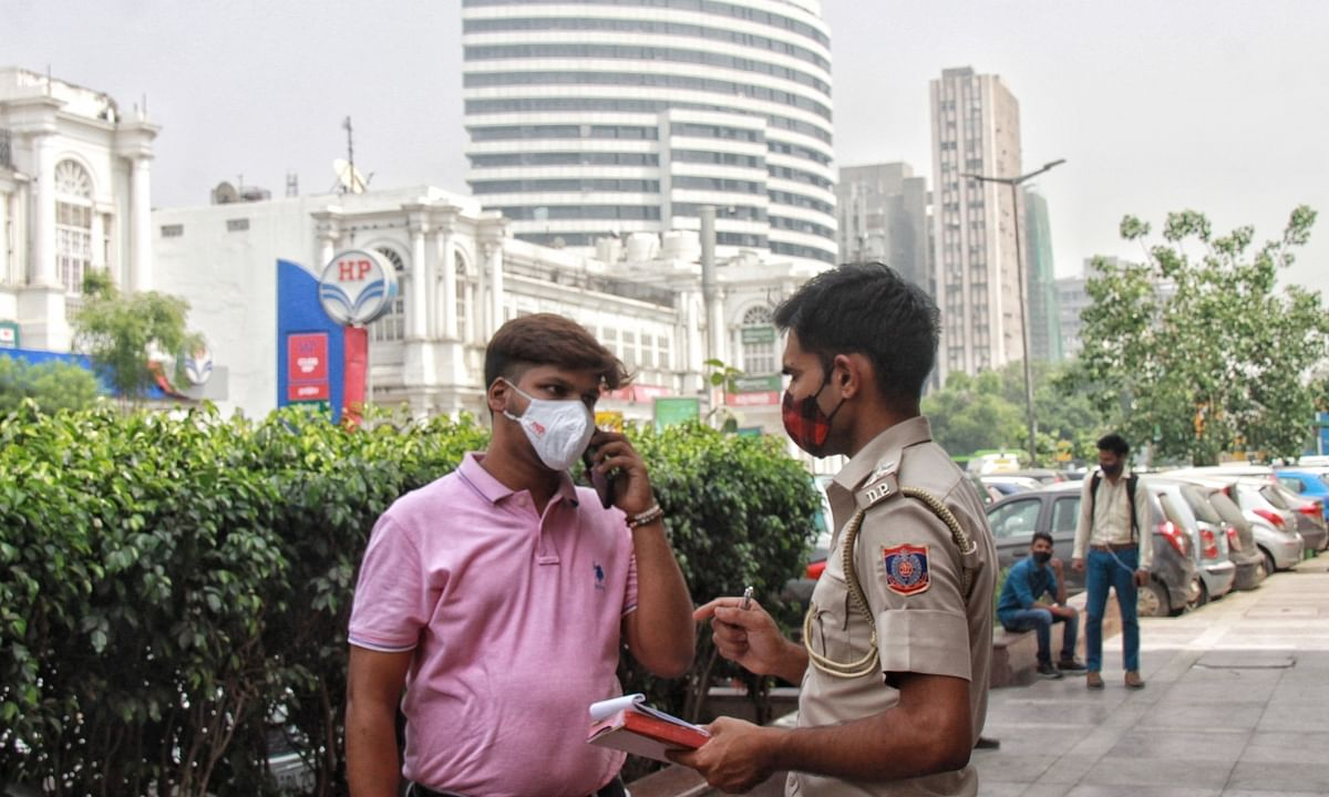 Delhi Police personnel imposing fines on people not wearing face marks, in violation of COVID-19 ruules, at Connaught Place in New Delhi, on April 6, 2021.