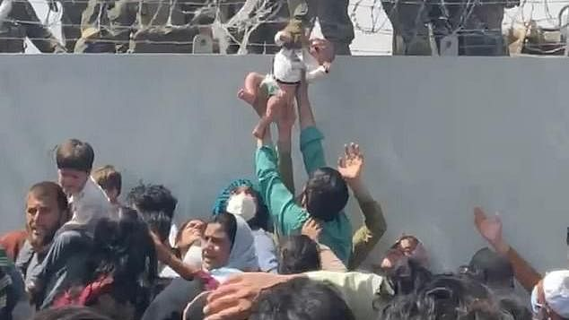 Baby passed over a wall at Kabul airport reunited with family