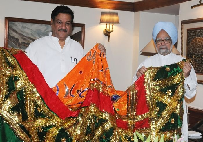 Prime Minister Manmohan Singh handing over the 'Chaadar' to be offered at the dargah of Khwaja Moinuddin Chishti, Ajmer Sharif to the Minister of State for the PMO Prithviraj Chavan in New Delhi on Thursday.