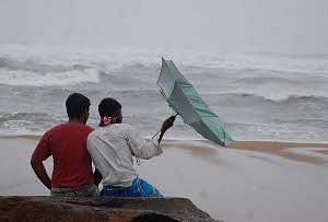 Fishermen watching the high waves at Marina beach following authorities warning them not to venture into the sea due to cyclonic storm Thane, in Chennai on December 29, 2011. UNI PHOTO