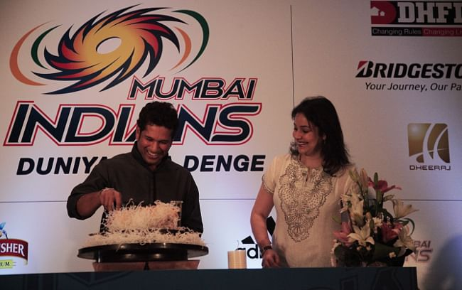 Cricketer Sachin Tendulkar cutting a cake to mark his 40th birthday in Mumbai on April 24, 2013 as his wife Anjali watches on.