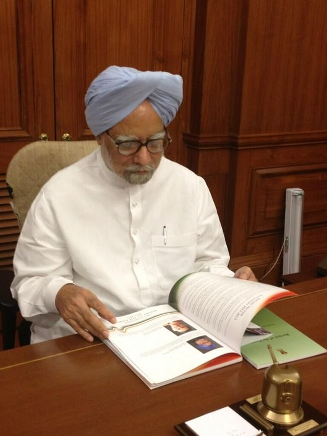 Prime Minister Manmohan Singh looks at the first copy of the 'Report to The People 2013'  of the United Progressive Alliance (UPA) Government in New Delhi on May 22, 2013.  The report will be released later tonight.