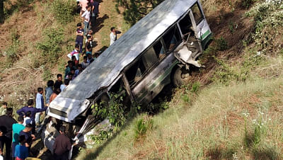 Locals gather at the site where a state-run bus of a private school rolled down into a gorge, at Lower Khalini in Shimla, on July 1, 2019.