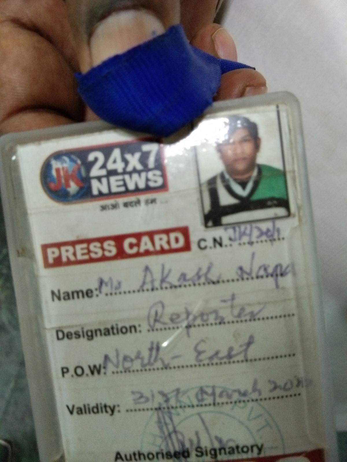 Akash Napa's father shows his son's press card.