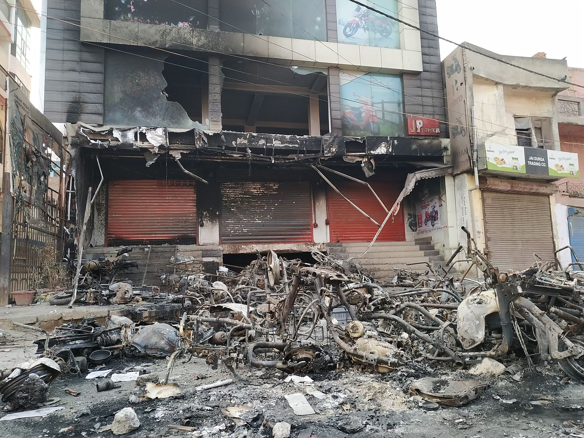 A burnt motorcycle showroom on the Karawal Nagar main road.