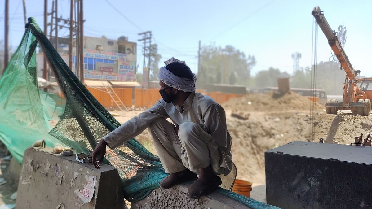 A worker waits for his bus at Lal Kuan