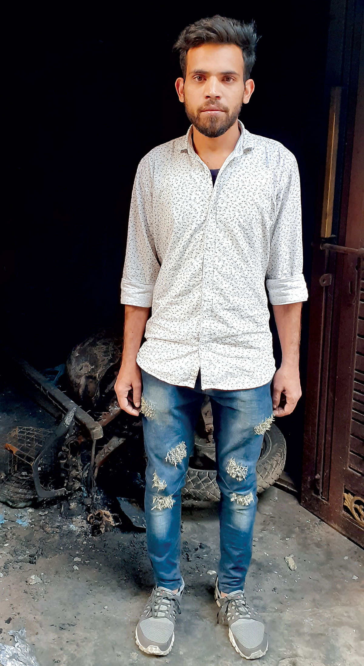 Irshad Ali in front of his burnt house.
