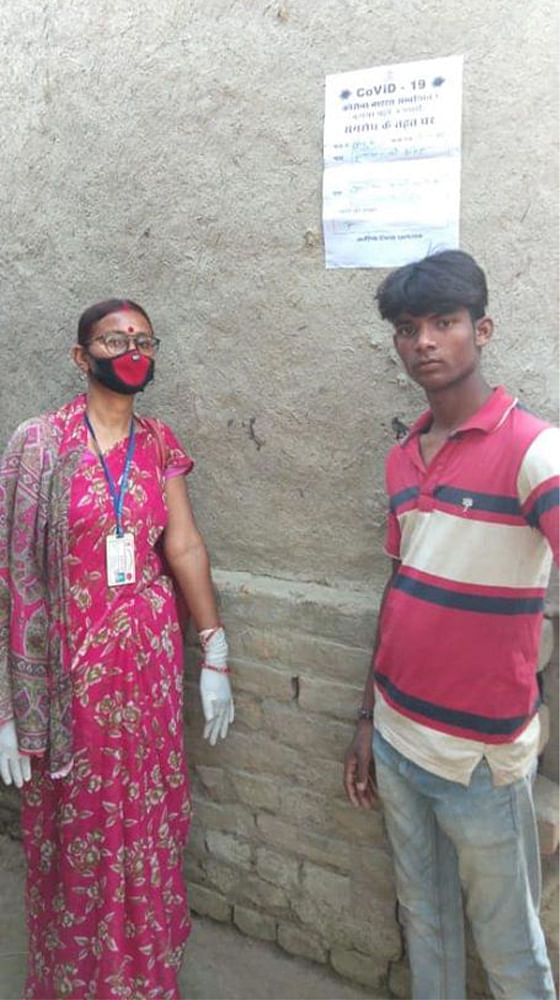 Kiran Jha, an ASHA trainer from Araria district, with a migrant worker who has to be quaratined. A notice has been stuck on the walls of his house.