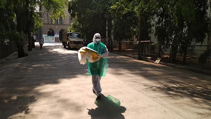 A morgue assistant carrying a sheet to wrap a dead body.