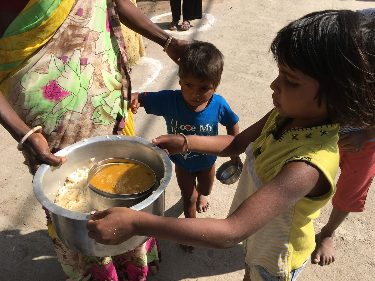 A child collects cooked a meal rice and chickpeas at Kapasheda border near Haryana for her family.