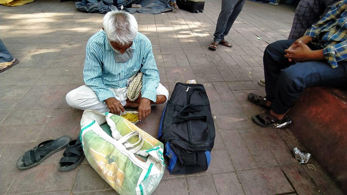 जमीन पर बैठकर खाना खाते बुजुर्ग सरयुग प्रसाद